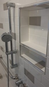accessible shower renovated that featured a white subway tile wall interspersed with some gray subway tiles
