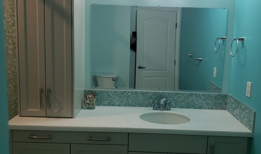 Small renovated condo bathroom with aquamarine walls & shaker color cabinets with a Corian countertop.