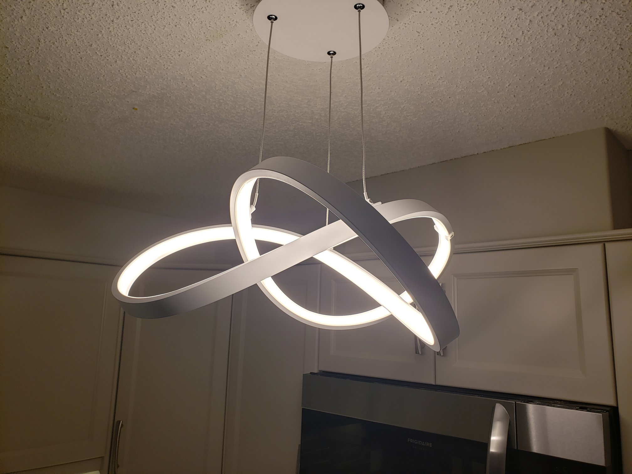 The kitchen used to have tacky track lighting. She chose this beautiful LED fixture to replace it. Along with the undercabinet lighting, the kitchen is bright and well lit.