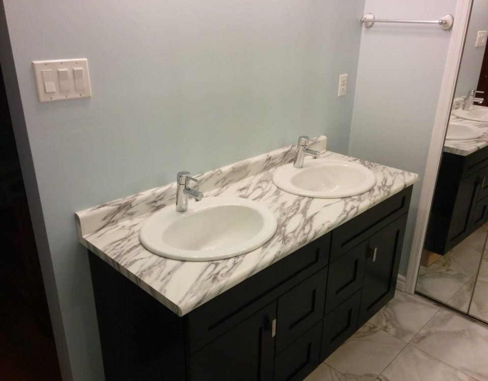 Stained maple vanity, laminate counter top, and higher end sink bowls and taps. The client also chose luxury vinyl tile to complement the rest of the bathroom