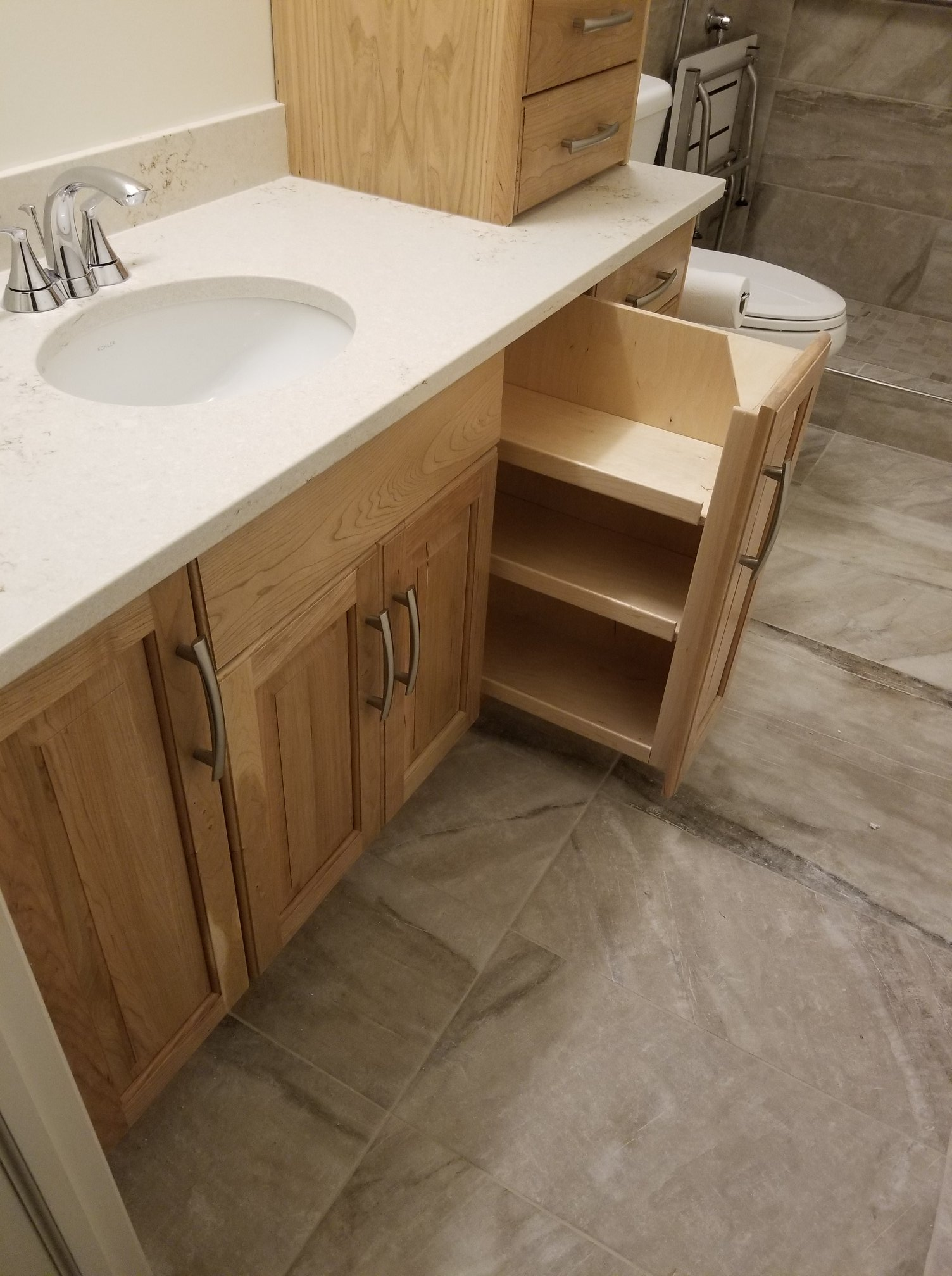 The vanity, with a clear cherry finish, has some really nice features, such as two put out shelf units. One of the complaints about the original vanity was the difficultly in reaching the items stored in the back. These pull out drawers solve that problem easily