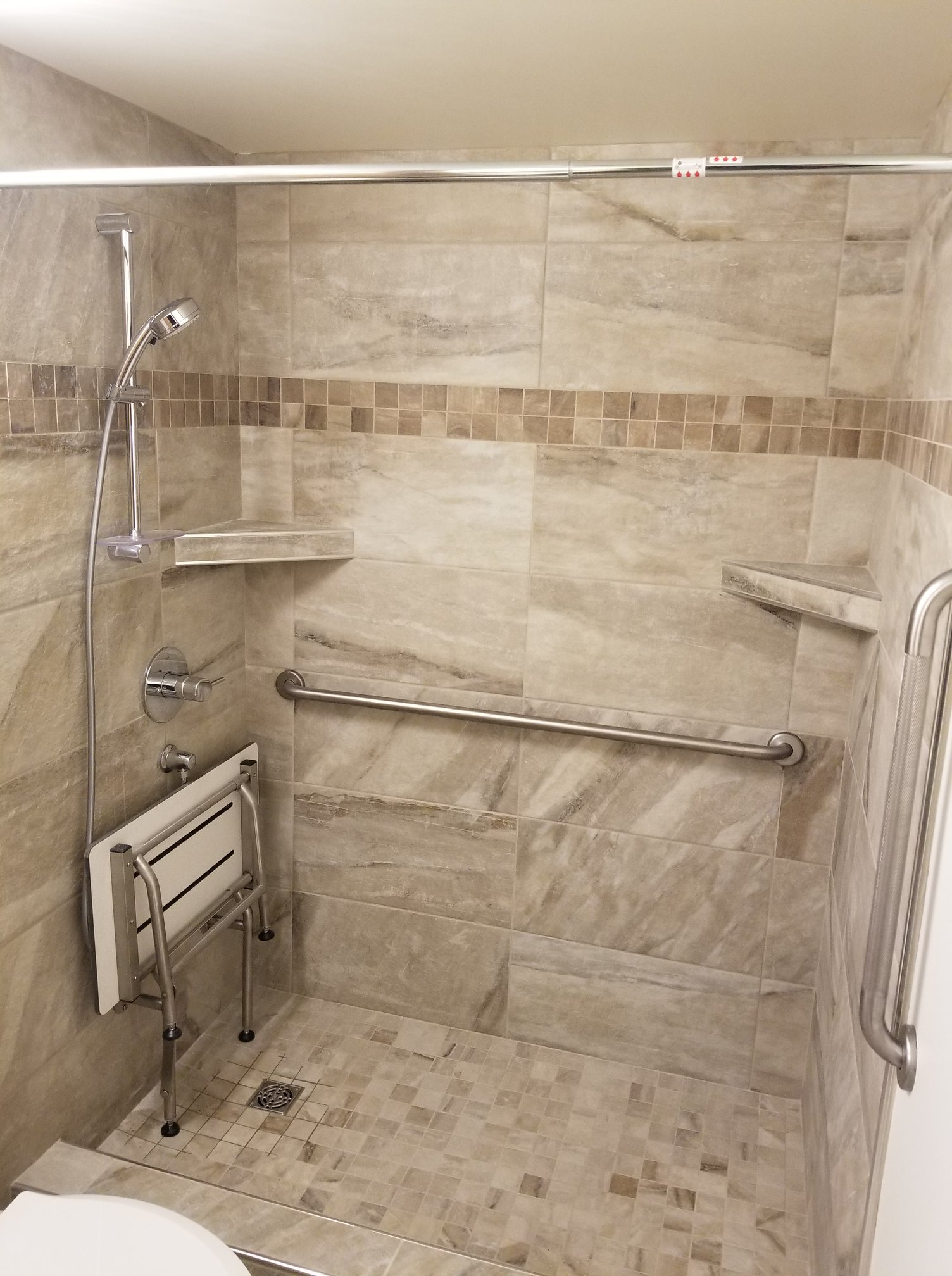 """The shower features some very beautiful tile work as well as the fold down phenolic resin bench. The wall tile is 12""""x24"""" Pearl Almond with 2""""x2"""" Pearl Camel mosaic accent. The floor tile in the shower is a matching 2""""x2"""" Pearl Almond mosaic. The client also chose a Grohe Tempesta Cosmopolitan shower rail set with a Grohe shower valve and Concetto Chrome Trim."""