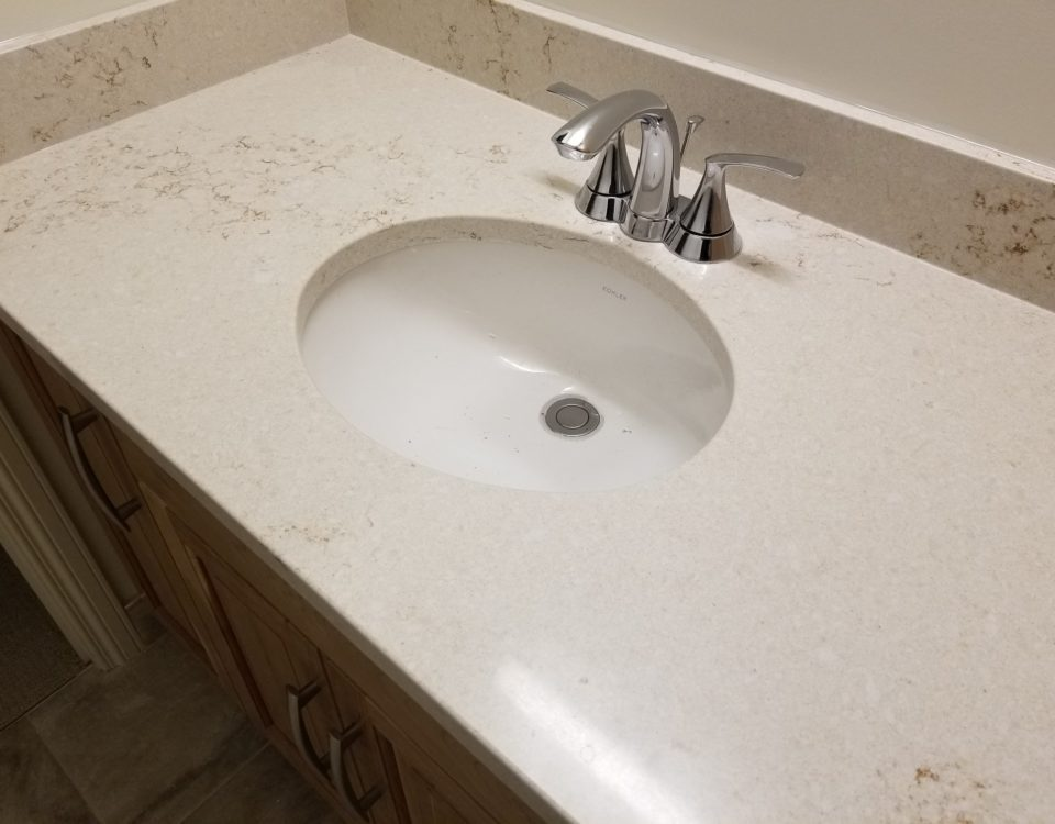 This beautiful counter top is a quartz Hanstone top and the color is Serenity. It's coupled with a Kohler undermount sink and a Moen Darcy faucet.